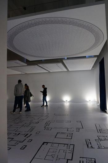 Rear view of people walking on tiled floor