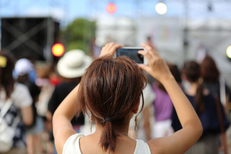 Rear View Of Woman Photographing People Through Smart Phone