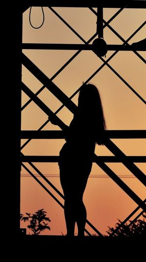 Silhouette woman standing against sunset sky