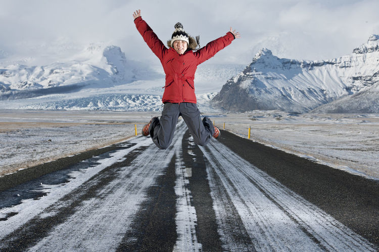 Man with arms outstretched on snowcapped mountain