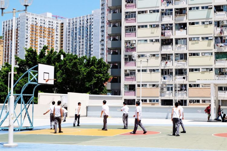 Boys Playing Basketball Against Buildings In City