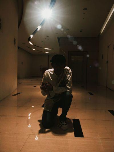 Full length of man sitting on floor in illuminated building