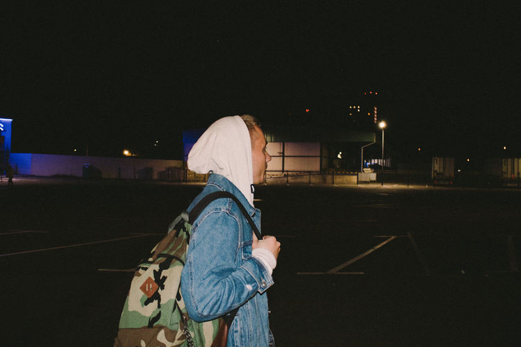 Side view of man with backpack standing in parking lot