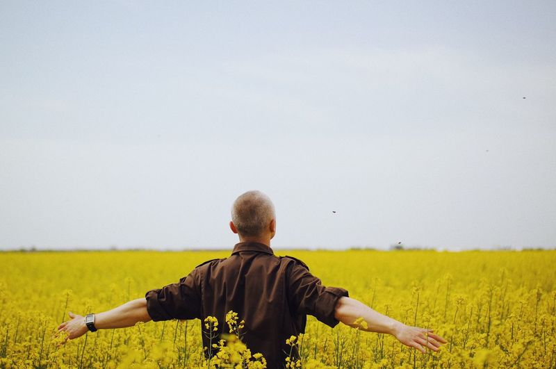 Rear view of man standing on rapeseed field against sky