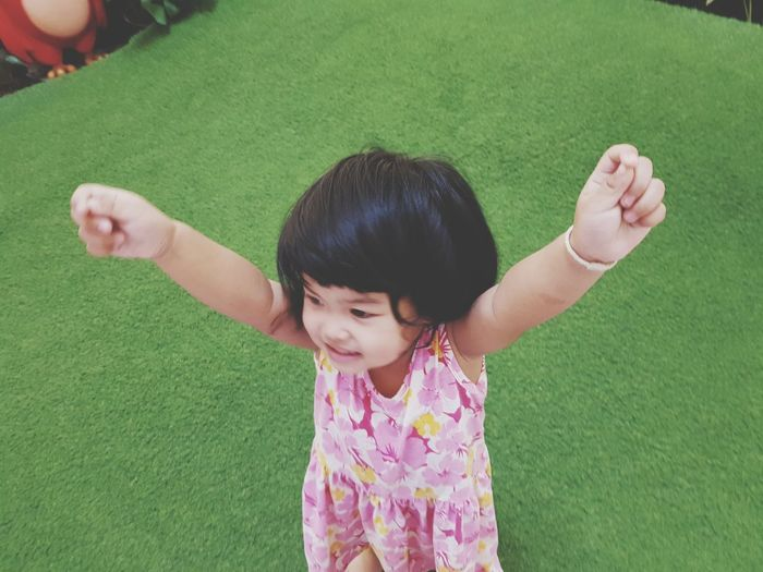 High angle view of cute girl with arms raised standing on turf