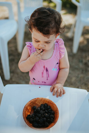 Baby girl eating blackberry