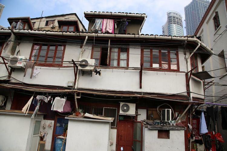 Old house beneath the skyline of Pudong in Shanghai Air Condition Architecture Balcon Balcony Building Exterior Built Structure Day Housing Housing Settlement Low Angle View No People Old House Old House China Outdoors Shack Sky Window