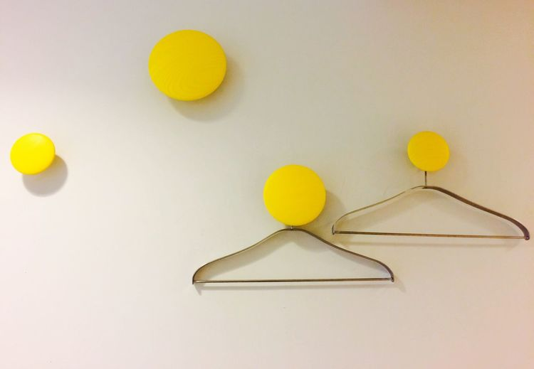 Coathangers Hanging From Yellow Knobs Mounted On White Wall