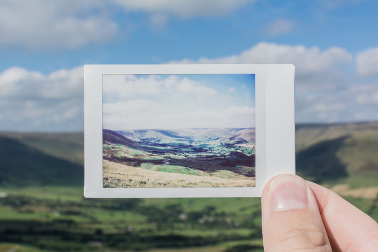 Close-up of person holding instant camera picture of hills against cloudy sky