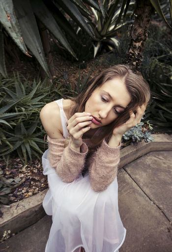 Young woman sitting against succulent plants