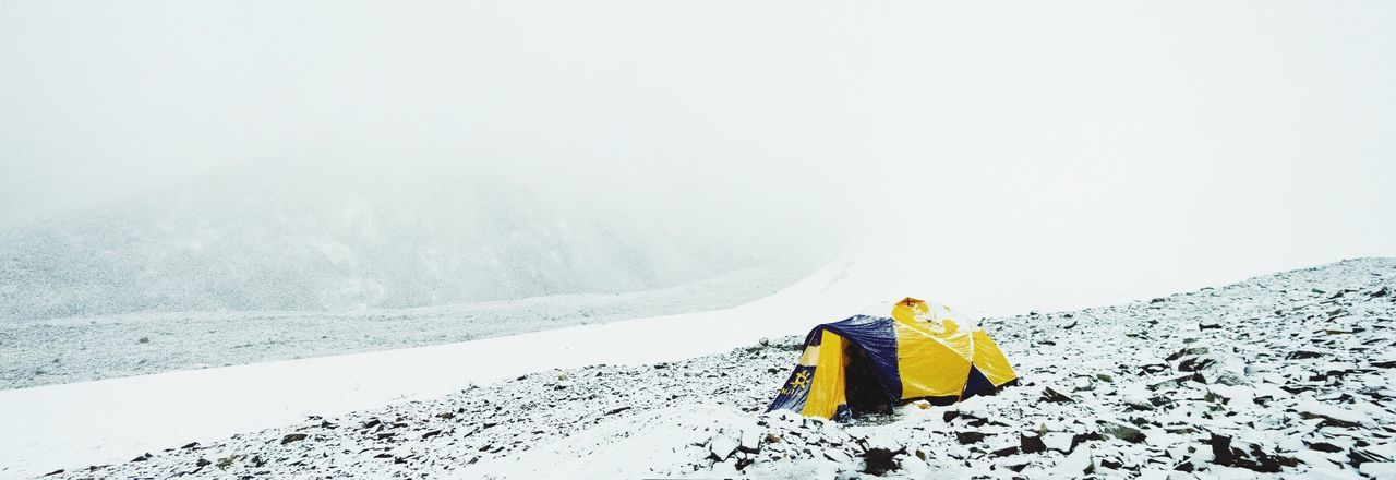 Panoramic shot of tent on stones at mountain during winter