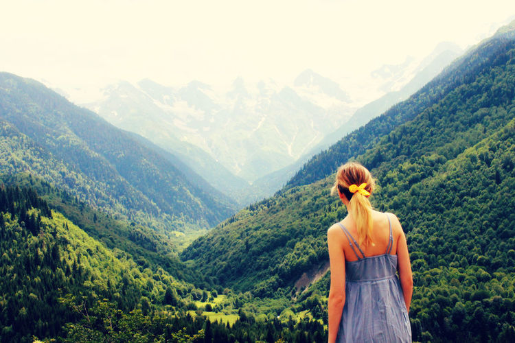 Rear View Of Woman Standing In Front Of Mountains
