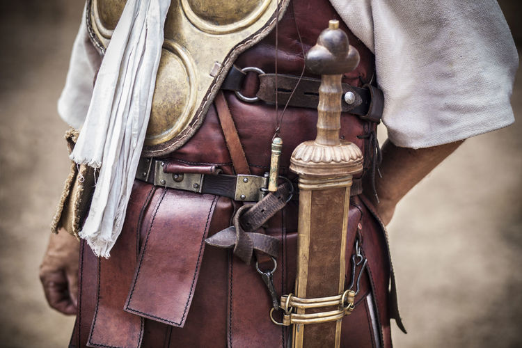Midsection of man wearing leather armor with weapons