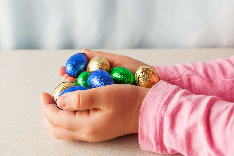 Child's hands holding chocolate Easter eggs wrapped in colorful foil with copy space. Side view. Chocolate Easter Easter Eggs Sugar Sugar Coated Candy Celebration Close-up Closeup Day Easter Easter Egg Food Happy Easter Human Body Part Human Hand Indoors  Multi Colored One Person People Real People Sweet Food