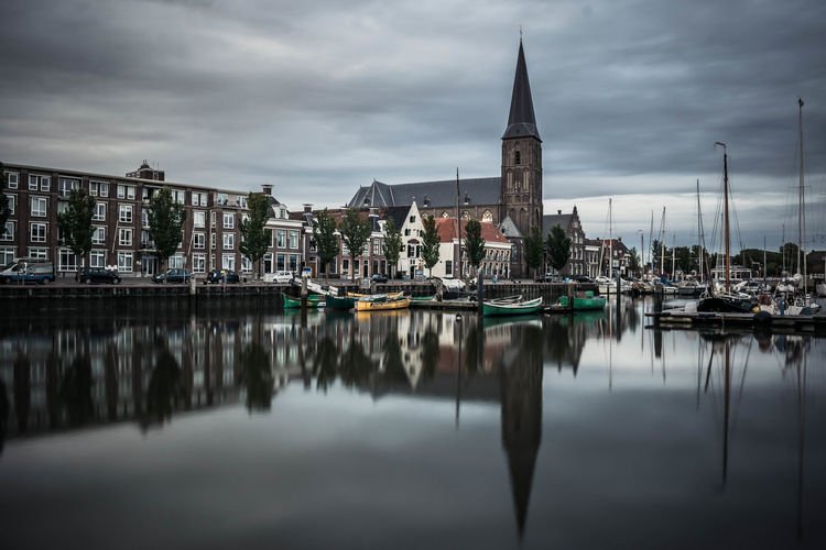 Sailboats Moored On River By Buildings Against Cloudy Sky