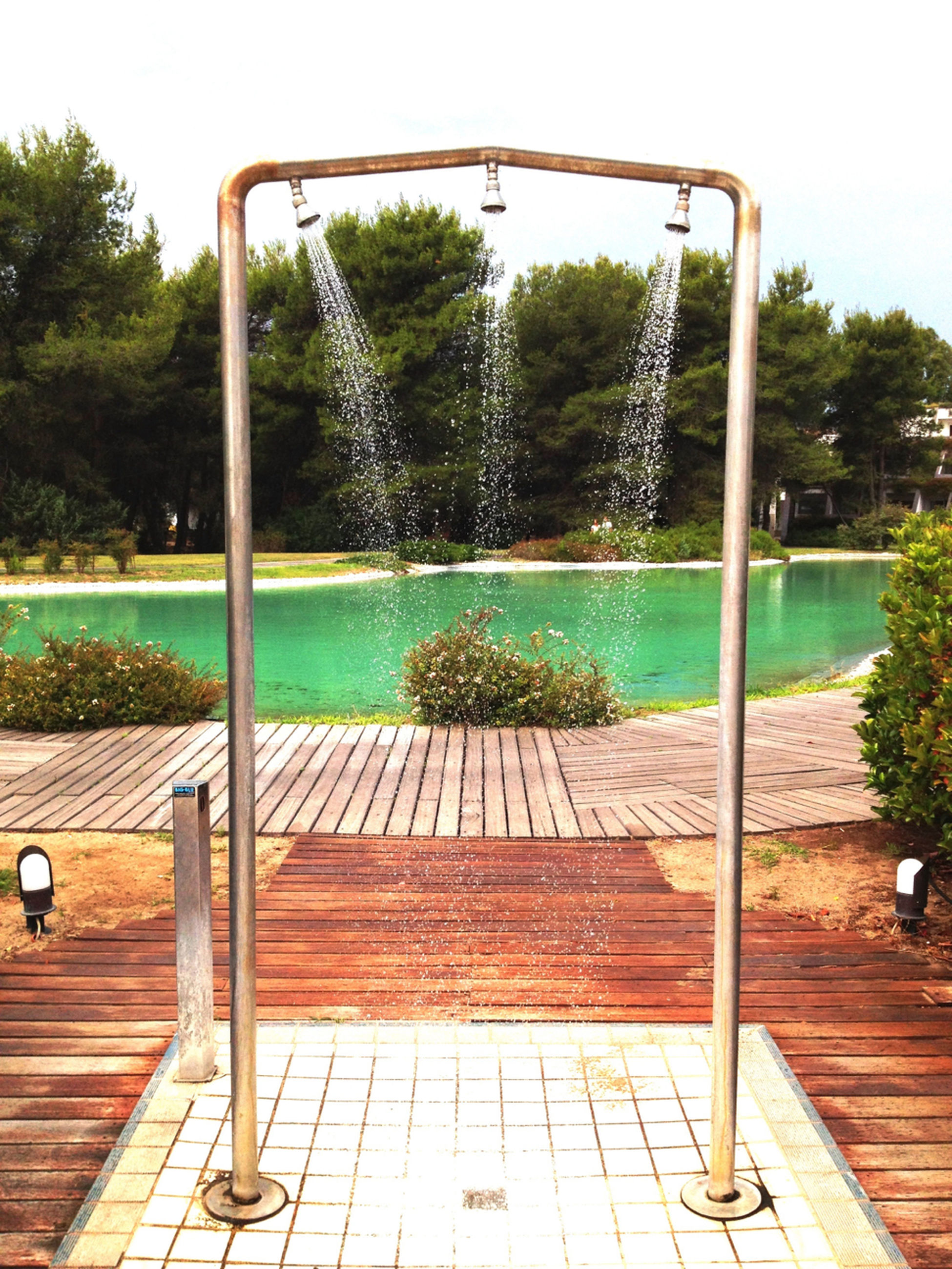 tree, water, swimming pool, railing, wood - material, park - man made space, day, sky, sunlight, nature, built structure, tranquility, clear sky, gazebo, blue, sea, absence, outdoors, pier, green color