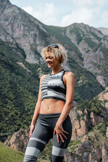 Smiling young woman standing against mountain range