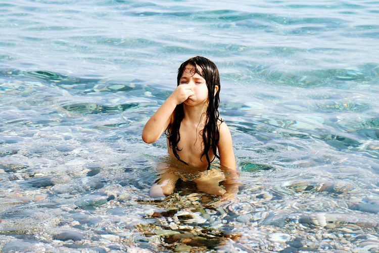 High angle view of topless girl holding nose in water at beach