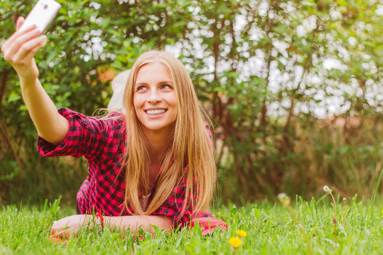 Smiling young woman taking selfie with mobile phone in park