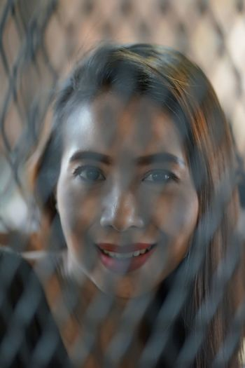 Close-up portrait of smiling mature woman seen through fence