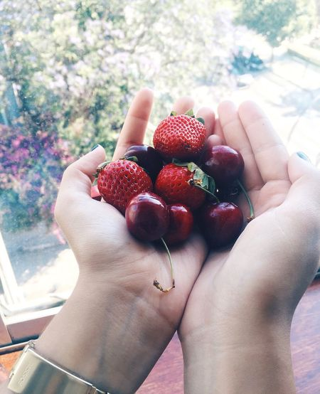 Close-up of cropped hands holding strawberries and cherries at home