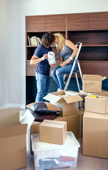 Young Couple Kissing By Cardboard Boxes At Home
