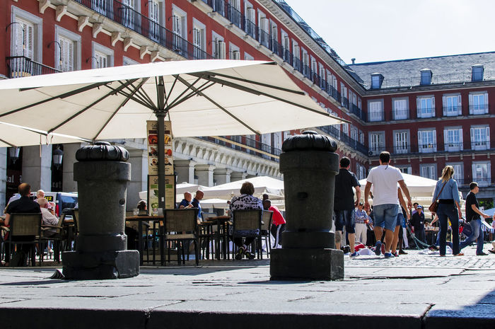 An terrazza in Plaza Mayor in Madrid. Architecture Building Exterior Built Structure Chairs City City City Life Day Large Group Of People Lifestyles Men Outdoors Outside Plaza Mayor Real People Restaurant Sky Sun Umbrella Table Terrazza Tourism Travel Travel Destinations Traveling Women