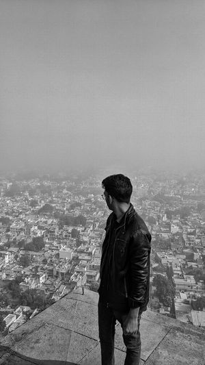 Young man standing over city buildings against sky