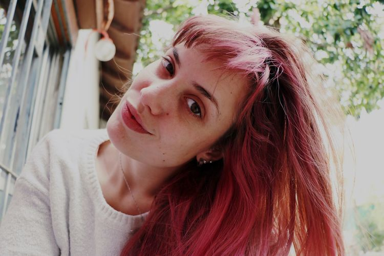 Low Angle Portrait Of Young Woman With Dyed Hair At Backyard
