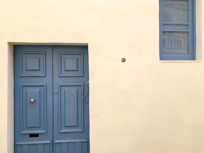 Closed gray door and window amidst beige wall