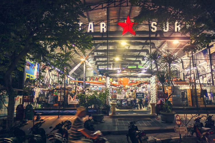a surfing shop in Kuta, Bali, Indonesia ASIA Bali, Indonesia EyeEmNewHere Kuta Shopping Architecture Building Exterior Built Structure City Crowd Flag Illuminated Large Group Of People Legian Lifestyles Mall Men Night Outdoors People Real People Street Photography Surfing Surfing Shop Tree