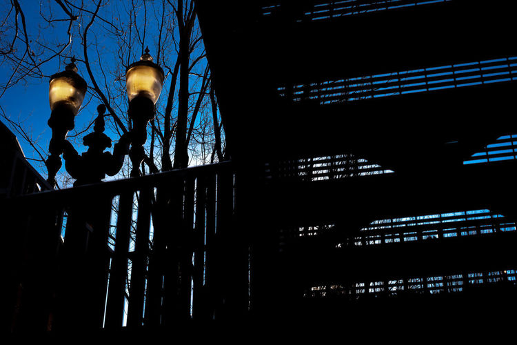 Low angle view of silhouette illuminated railing against blue sky