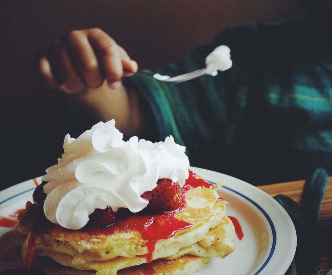 Midsection of child holding fork over pancake on table