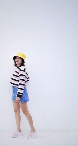 Full length of cute boy standing against white background