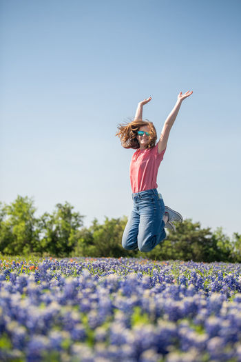 Woman with arms outstretched on field against blue sky