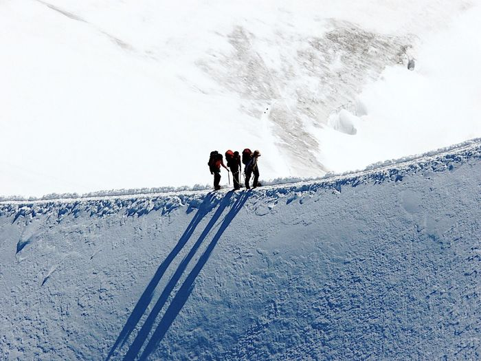 Hikers Walking On Ridge Of Snowcapped Mountain