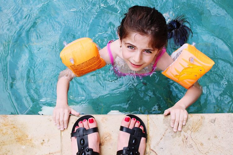 Low section of mother with daughter swimming in pool