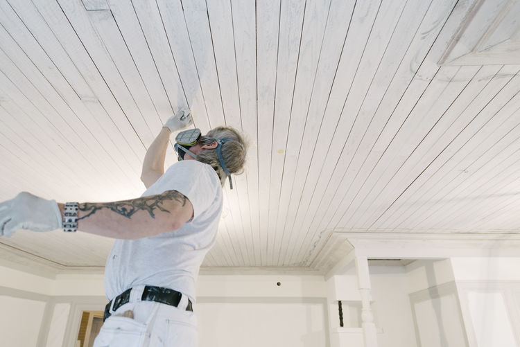 Low angle view of man standing on ceiling