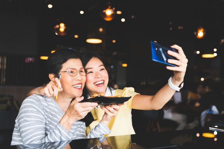 Bangkok, Thailand - Aug 28, 2018: Asian mother and daughter taking selfie photo together with food at restaurant, using S-Pen bluetooth remote shutter on Samsung Galaxy Note 9. Illustrative editorial. Asian  Family Japanese  Korean Laughing Love Mother Mother & Daughter Note 9 Samsung Samsung Galaxy Note Samsung Galaxy Note 9 Samsung Mobile Photography Chinese Daughter Food Illustrative Editorial Laugh Remote Restaurant S Pen Selfie Smartphone Smartphone Photography Smiling