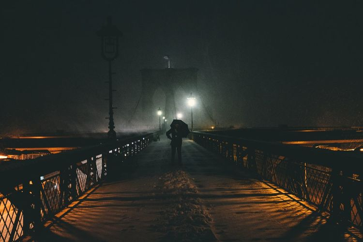 Mid distance view of person standing on brooklyn bridge at night