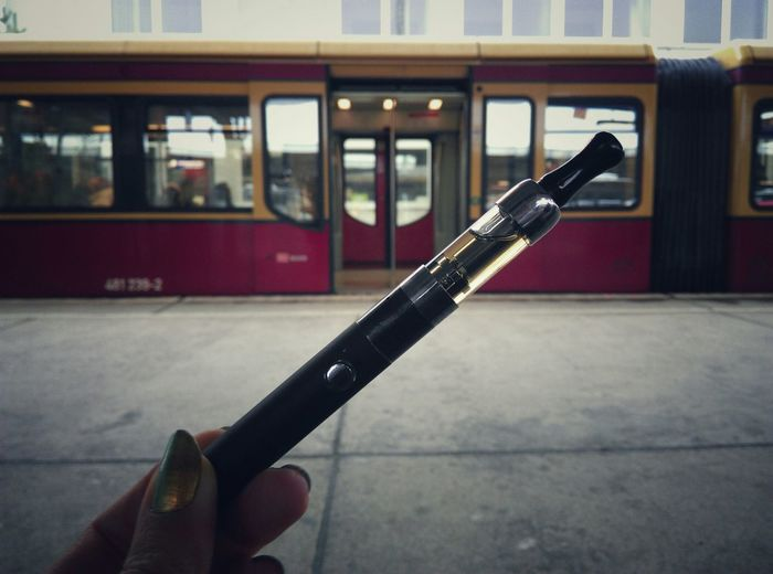 Cropped image of hand holding electronic cigarette at railroad station
