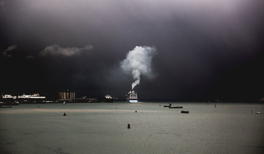 Cruise leaving Southampton port in storm weatherfrom his chimney rises white smoke contrasting to dark sky Contrasting Colors Cruise Dark Diesel Dramatic Sky Dull Fear Ferry Ferry Boat Going On Holiday Heavy Industrial Mud Nature Ocean Scary Sea Ship Sky Smoke Storm White Smoke