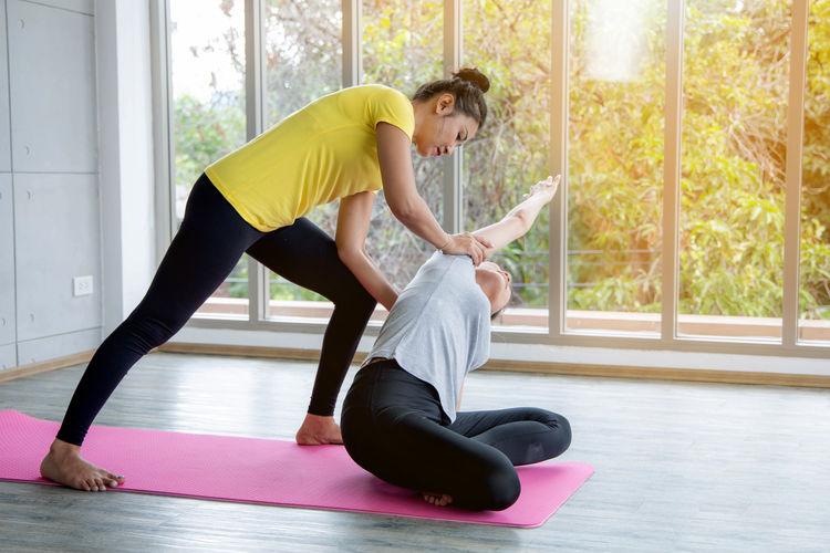 Women assisting friend yoga against window
