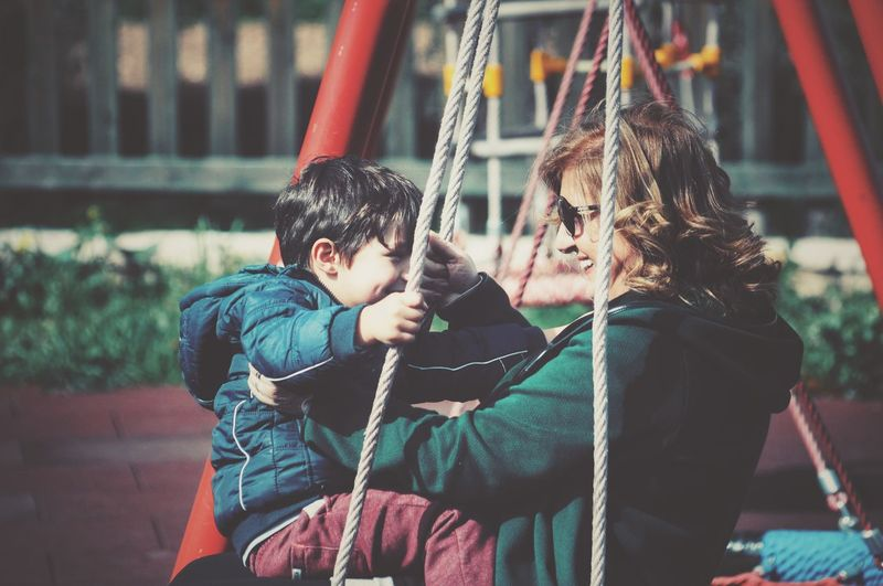 Side view of grandmother with grandson sitting on swing at playground