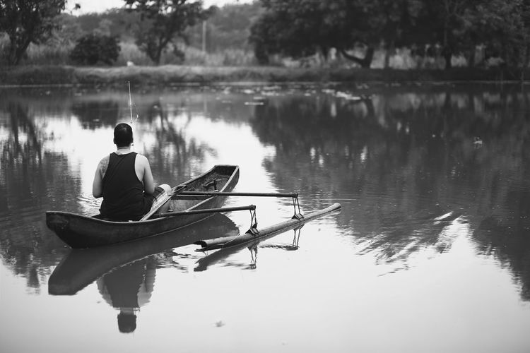 Rear View Of Man Fishing On Outrigger Over Lake