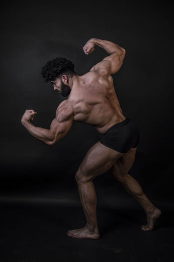 Rear view of shirtless bodybuilder against black background