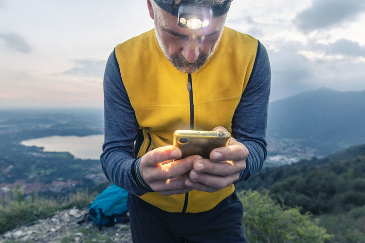 Midsection of man holding mobile phone against mountains