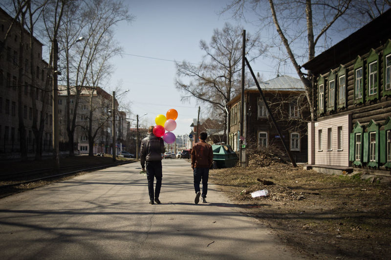 Rear view of man with balloons walking by friend on road in city