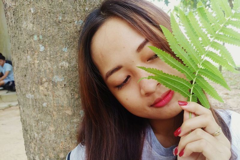 Close-up of young woman holding fern