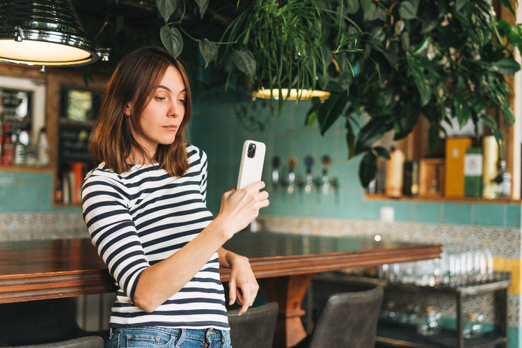 Young woman using smart phone while standing on camera